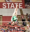 Valparaiso's Lia Milroy looks to stick her dismount off the uneven bars Saturday afternoon at the state gymnastics meet in Muncie.