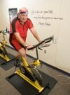 Jerry Stein on Indoor Cycle with Charles Schulz Wall Quote