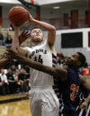 Lowell's Jayson Savich shoots over West Side's Ramone Adkins on Saturday.