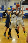 Marian Catholic center Kaitlyn Sedor, right, and forward Ashton Millender battle for possession of the basketball with Sandburg forward Victoria Stavropoulos during Thursday night's Class 4A regional championship.