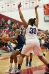 Michigan City senior Aubria Smith attempts to shoot past Merrillville senior forward Amber Sturdivant