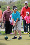 Aidan Gutierrez, 8, lines up a putt during a clinic and demonstration with professional golfer Fuzzy Zoeller on Saturday at Creekside Golf Course and Learning Center, which is celebrating the 15th anniversary of its First Tee program.