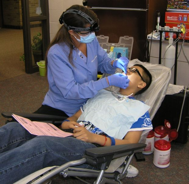 mobile dentist cleans teeth  gets smiles from mis students