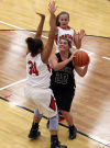 Lowell's Hunter Jusevich looks to shoot while Portage's Lindsay Givens, left, and Hannah Piro defend