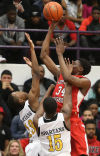 Homewood-Flossmoor's Tai Odiase shoots against Marian Catholic's Ezra Pointer-Jones and John Oliver in Marian's win in the Class 4A Thornton Sectional final Friday.