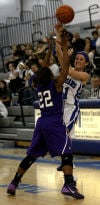 Lake Central's Tara Zlotkowski passes over Merrillville's A.J. Downs on Friday.