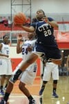 Michigan City senior forward Jameka Collins drives past Merrillville senior guard Darian Patton