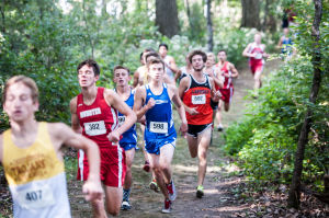 Boys runners trek through the wooded area of the course