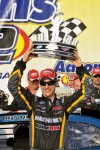 Joey Logano hoists the trophy in victory lane