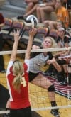 Lowell's Ashley DeBoer tries to spike over the block attempt of Andrean's Marija Nicksic on Thursday.