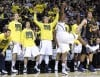 Michigan players watch a Glenn Robinson III 3-pointer