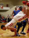Crown Point's Mike Wathier goes head first onto the floor, falling over Lake Central's Tye Wilburn on Friday night.