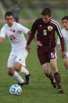 Munster's Sean Pruzin, left, and Chesterton's Michael James chase down the ball during Thursday's semifinals of the Class 2A Merrillville Regional.