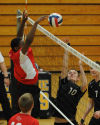 Homewood Flossmoor's Marques Robinson tips as Marian's Zak Piekarski, right, attempts a block at Marian Catholic on Tuesday.