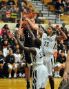 Griffith's Erick Johnson and Tremell Murphy foul Lowell's Eric Zukauskas under the basket Tuesday night.
