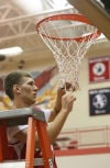 Hebron's Tony Rose cuts down the net after the Hawks won the PCC tourney title.