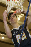 Nathan Flores cuts a piece of the net after Marquette Catholic beat Liberty Christian for the Class A Northern Semistate title.