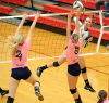 Valparaiso's Noelle Eveland spikes form the corner against the block of Michigan City's Claire Powers, left, and Autumn Kinney on Thursday.