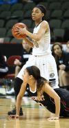Purdue Calumet's Tierra Turner passes the ball as Davenport's Shaina Johnson falls during Friday's second round of the NAIA Division II tournament at the Tyson Events Center in Sioux City, Iowa.