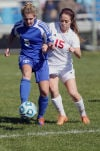 Lake Central's Hannah Triveline and Munster's Lexie Lyons chase down a ball