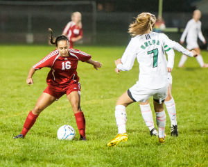 Munster's Jessica Flores covers the ball as the Valparaiso defense closes in Thursday.