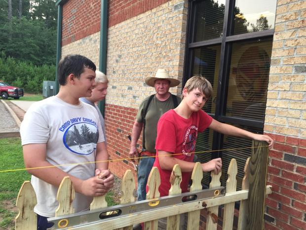 <p>Trenton Dailey, right, along with the help of friends and family, built a fence at High Shoals Elementary School between the garden and playground.</p>