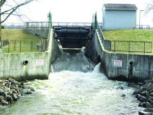 <p>Water pouring through the Buckeye Lake dam. The state recently announced a five-year plan to repair the dam which will require the lowering of water levels in the lake. The economic impact could affect all of Perry County.</p>