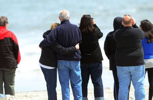 Boat: Family members hug on the beach in Ocean City as the boat is raised. Sunday April 28 2013 (The Press of Atlantic City / Ben Fogletto)  - Photo by Ben Fogletto