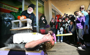 SWORD SWALLOWERS: Gary Peyre-Ferry smashes a pumpkin on the chest of David Peyre-Ferry of Oxford Pa., as he demonstrates sword swallowing at Ripley's Believe it or Not in Atlantic City. Saturday February 22 2014 Ripley museums across the nation simultaneously hosted sword swallowing events at precisely 2:22:14 pm. (The Press of Atlantic City / Ben Fogletto) - Ben Fogletto