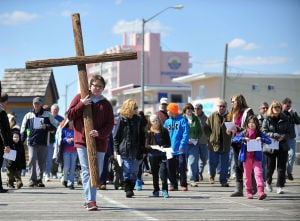 Station Of The Cross: Devin Mulloy, 16, of the Bargaintown section of Egg Harbor Township, carries a wooden cross Friday on the Ocean City Boardwalk. Members of St. John Lutheran Church of Ocean City held the event in observation of Good Friday.  - Michael Ein