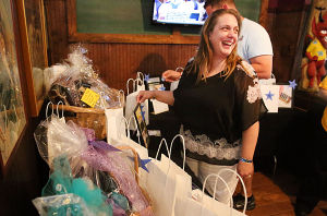 Mullica Teacher Benefit: Mullica kindergarten teacher Kelly Mascio looks at items gathered for the silent auction. Sunday April 13 2014 Fund raiser at JD's Pub in Smithville to help Mullica kindergarten teacher Kelly Mascio pay her bills while suspended without pay. (The Press of Atlantic City / Ben Fogletto) - Ben Fogletto