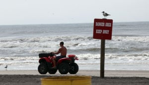 DANGER BEACH: A lifeguard passes a sign warning bathers at the beach at Dr. Martin Luther King, Jr., Boulevard, in Atlantic City, NJ, where two people drowned July 27, 2013. (Monday July 29, 2013.) - Vernon Ogrodnek