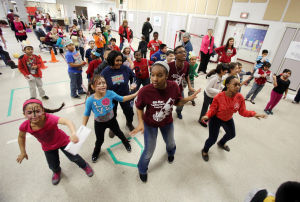 IN THE SCHOOLS CARNIVAL 100: Wildwood High School All Star Traiding Card students Zi'yairea Bryant (center) Majhadi Marrow (back) and Janessa Morgan (right), leads third grade students in a round of
