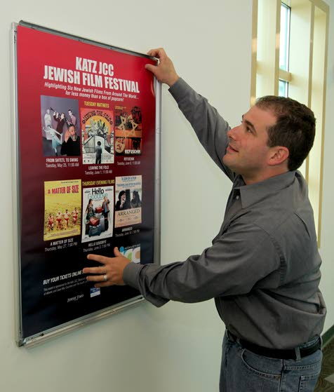 Josh Cutler of Margate City hangs a poster for the JCC FILM FESTIVAL in the Jewish Community Center in Margate City on Tuesday May 11