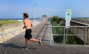 Open Space: A jogger passes the pier and a sign designating the pier as a Green Acres site. Monday July 29 2013 Ventnor Pier related to open space measure that was up for a vote in the senate on Monday. (The Press of Atlantic City / Ben Fogletto) - Ben Fogletto