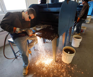 Votech Training: Junior Ryan Schubert of Middle Township, uses a cutting torch to cut metal in Tom Jackson's welding class. Students at Cape May County Technical High School prepare for certification testing in programs that include welding, automotive technology, engineering and culinary arts. - Dale Gerhard