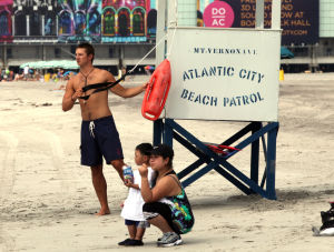 DANGER BEACH: J.B. Magee, an Atlantic City lifeguard from Brigantine, directs bathers in the water off Mt. Vernon Avenue, in Atlantic City, NJ, a block away from where two people drowned this weekend, Monday July 29, 2013. Lifeguards were keeping bathers to their waist and away from rip currents Monday. - Vernon Ogrodnek