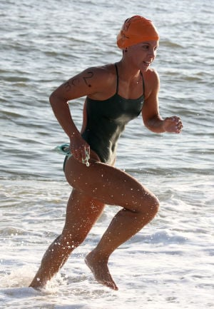: Cape May's Meghan O'Leary, exits the water at the end of the swim. Cape May Point Women's Lifeguard Challenge, a short run-paddleboard-swim triathlon for women lifeguards Monday July 29, 2013. (Dale Gerhard Photo/Press of Atlantic City) - Dale Gerhard