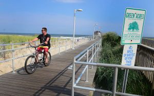 Open Space: Frank Walsh of Ventnor rides the pier near a sign designating the pier as a Green Acres site. Monday July 29 2013 Ventnor Pier related to open space measure that was up for a vote in the senate on Monday. (The Press of Atlantic City / Ben Fogletto) - Ben Fogletto