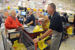 Helping To Bag Hunger: Foodbank representitive Andy Applegate, of Absecon, helped bag groceries for Hilda Cetin, of Galloway Township, as cashier Gabriela Bracero, of Galloway, watched during the Help Bag Hunger event at the ShopRite on South Pitney Road in Galloway. - Dave Griffin