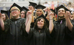 Stockton Graduation: (l-r front) Graduates Clayto Rossner of Cape May, Crystal Semegran of Point Pleasant Beach and Rich Steinmann of Galloway hold hands with the rest of the class as they sing the Alma Matter at the end of the ceremony. Sunday May 11 2014 Stockton College Graduation, morning session. (The Press of Atlantic City / Ben Fogletto) - Ben Fogletto
