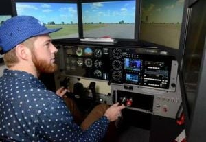 "Aviation: Atlantic Cape Community College student, Luke Peterson, of the Cardiff section of Egg Harbor Township, checks the right side of the ""plane"" as he taxis down the runway in a flight simulator. Atlantic Cape Community College students using a flight simulator at Atlantic City International Airport, in Egg Harbor Township, as part of ACCC's aviation program.  - Danny Drake"