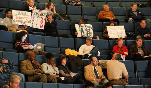 Sandy Recovery Hearing: Audience members hold protest signs during the meeting. - Photo by Ben Fogletto
