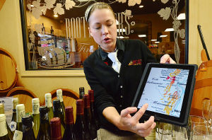 Bourgeios Wine: Elena Pahrabniak, of Ocean City, uses an app on an iPad at Bootleggers Liquor Outlet in Northfield to explain the wines being tasted Saturday.  - Photo by Ben Fogletto