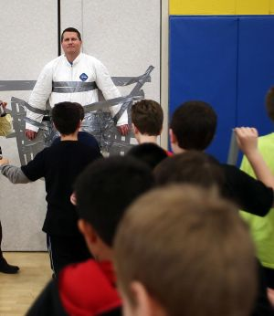 BOOK THE PRINCIPAL: Students at Northfield Middle School duct-taping principal Glenn Robbins to the gym wall and covering him in book covers as part of school challenge Friday, Feb 2, 2014. - Edward Lea