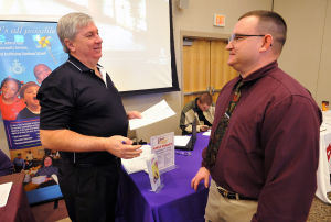 CUMBOVETS: Bruce Schaefer, of Galloway Township, representing Prince Telecom, left, accepts an application from Army veteran Sam Welden, of the Cedarville section of Lawrence Township, Wednesday during a Veterans Job Fair at Cumberland Community College in Vineland.  - Michael Ein