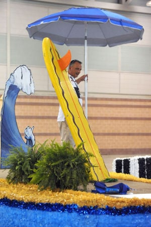 MISS AMERICA PARADE ADVANCE: Todd Marcocci, of West Chester, Pa., installs a beach umbrella onto the Catalina Swimwear parade float Friday at the Atlantic City Convention Center ahead of Saturday's Miss America Show Us Your Shoes Parade. - Photo by Michael Ein