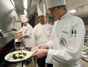 : Culinary instructor Jon Davies of West Cape May (center) watches over Jacob Lance of West Cape May, as he places his dish in the over to finish. The Cape campus of Atlantic Cape Community College in Cape May Court House, now offers a Culinary Arts Training Program. Wednesday April 3, 2013. (Dale Gerhard/The Press of Atlantic City)  - Dale Gerhard