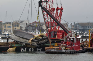 Missing Captain: The Cape Hatteras is lifted onto a barge Monday in the Intracoastal Waterway near Longport.  - Michael Ein