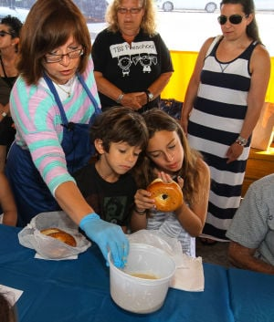 Acbp Y10 Challah Baking Class: Tova Rapoport showed Jack, 7, and Madison Barrack, 11, of Ventnor, a mixture of yeast and water as they started making challah bread. - kristian gonyea